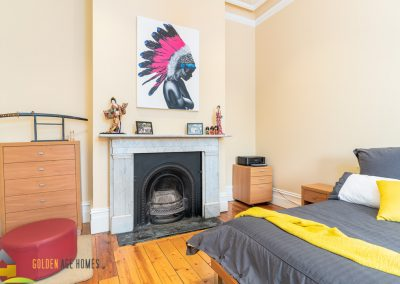 A cast iron firebox with marble mantle in bedroom 2 of the Bayview, a house for relocation