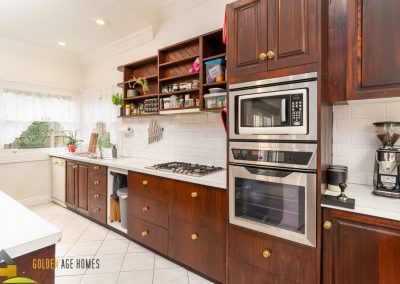 Stained timber kitchen with white tiles - The bayview, a house for relocation