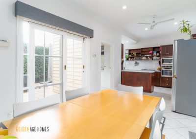 Looking over the dining table towards the kitchen offers views to outside.
