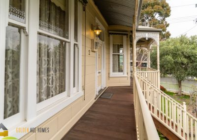 view from the front verandah looking towards the entry, highlighting the timber windows and concave roof with iron lacework.